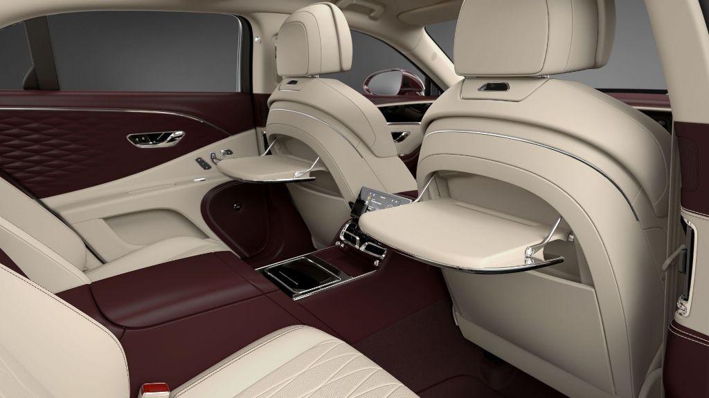 Для удобства задних пассажиров в спинки передних сидений вмонтированы столики с электроприводом и отделкой из деревянного шпона